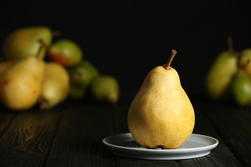 Plate with fresh ripe pear on table against blurred background