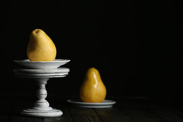 Stand with fresh ripe pear on table against dark background. Space for text