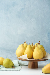 Stand with fresh ripe pears on table against color background