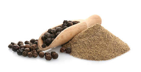 Wooden scoop with black pepper grains and heap of powder on white background