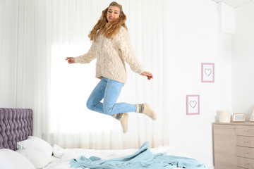 Attractive smiling young woman in cozy warm sweater jumping on bed at home