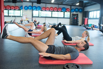 group of people training legs in a gym
