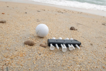 Golfer goes holiday at beach with golf ball and tee