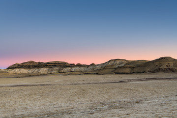 The desert landscape and hills of the Bisti Badlands of New Mexico at sunset under a beautiful sky with pink, peach, purple, and blue hues