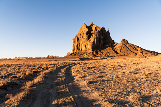 Road curving through a vast landscape to the rock formation of Shiprock in New Mexico