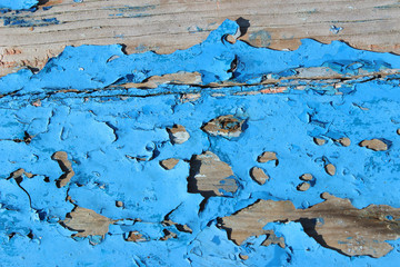 Peeling cracked old blue paint on wood plank texture surface detail close up horizontal abstract composition