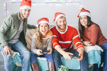 Happy couple of friends playing video games during christmas time at home - Young people having fun with new trends technologies console online - Entertainment, gaming and holidays concept