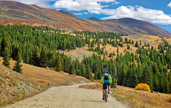 Bicyclist riding up Boreas Pass Road near Breckenridge, Colorado