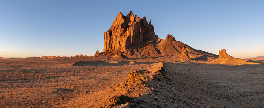Panorama of the Shiprock rock formation rising above a vast landscape in dramatic early morning light with a road winding toward the peak