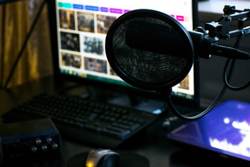 Closeup of professional Black Microphone in home recording studio with computer and audio production tools