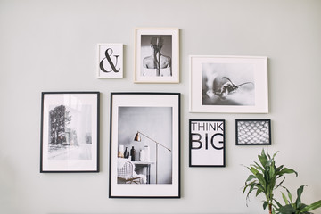 different size framed photos hanging on the gray wall. Papier Peint