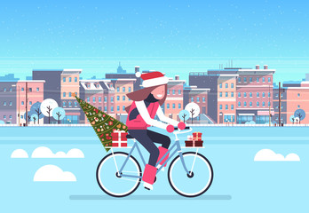 woman riding bike with fir tree gift box over city street buildings cityscape background merry christmas new year concept flat horizontal vector illustration