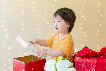Happy toddler boy with Christmas present boxes