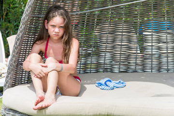 Sad girl in bathing suit sitting in wicker lounger hiding from the sun.