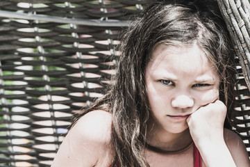 Angry girl in bathing suit with hand on face in wicker lounge chair.