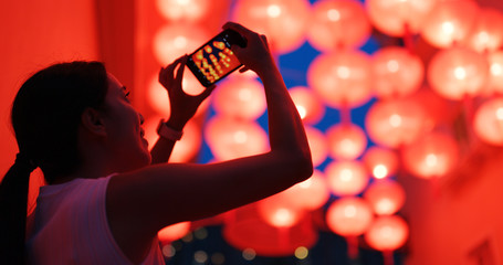 Woman take photo on cellphone with the red lantern