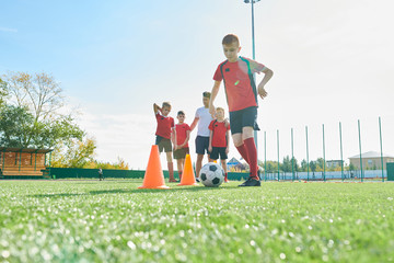 Full length portrait of junior football team training outdoors in sunlight with focus on boy leading ball between orange cones, copy space