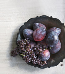 Plums and champagne grapes rest in a gray metal bowl on a light gray surface.