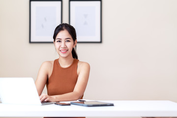 Attractive asian entrepreneur woman, happy student or young executive sitting on white desk table wearing casual orange vest dress smiling and looking at camera at home office with copy space.