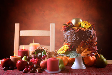 Beautiful Thanksgiving Fall table setting with Autumn theme chocolate cake, cornucopia and candles.