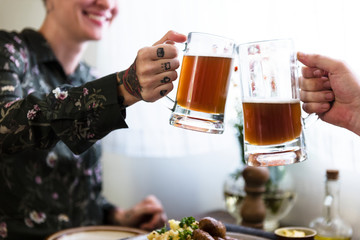 Happy women clinking with beer mugs
