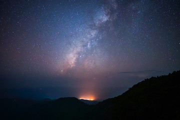 Milky way above the mountains peak with light from the village and noise