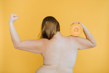 Strong blond woman holding a cantaloupe melon