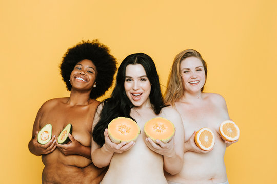 Diverse curvy nude women holding fruits over their breasts