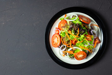 vegetable salad tomato, carrot, onion, spinach, and lettuce on black board