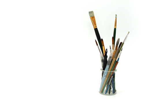 brush and other art tools in glass jar on white background