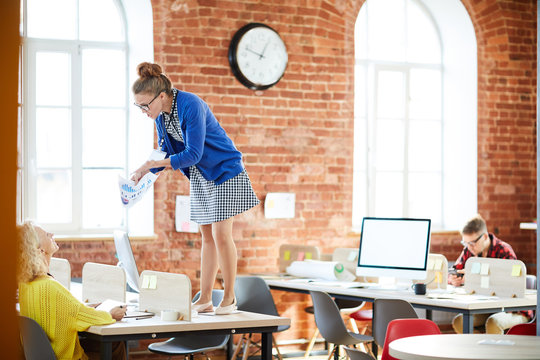 Angry young accountant with paper explaining financial data to her colleague while standing on table