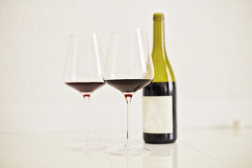 Red wine drinks in glasses with bottle on white background