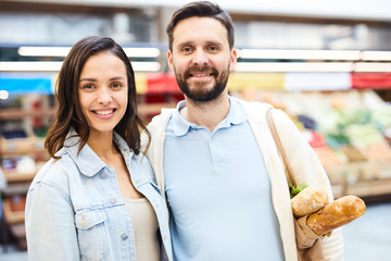 Happy positive young couple embracing and looking at camera while standing in food shop, smiling bearded man holding shopping bag on shoulder