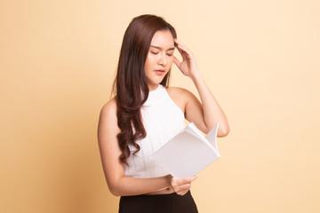 Young Asian woman got headache read a book.
