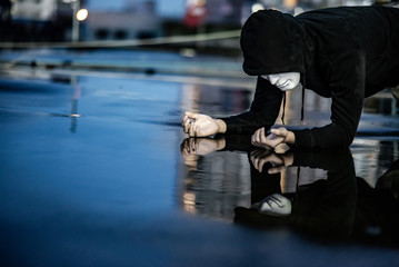 Reflection of mystery hoodie man in white mask feeling guilty looking his face on wet floor after the rain. Sadness, depression and surrender concepts