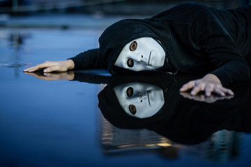 Reflection of mystery hoodie man in white mask feeling depressed and disappointed lying on wet floor after the rain. Sadness, depression and bipolar disorder concepts