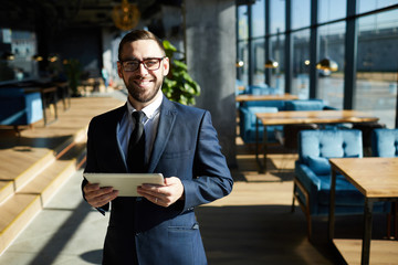 Cheerful man in suit using tablet while working in modern cafe on sunny day