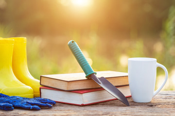 Cup of coffee, book, and garden equipment on wooden table with sunlight in morning time