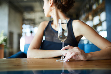 Young woman sitting by table in cafe and touching flute of champagne while looking over her shoulder