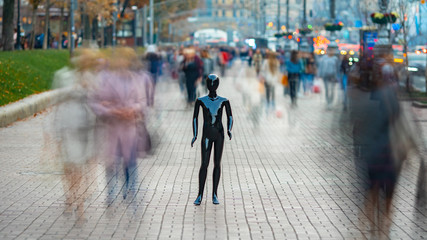 The dummy standing on the street among the stream of people