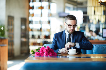 Elegant man having coffee while sitting by table in restaurant, looking at watch and waiting for girlfriend
