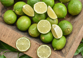 Fresh green lime with some slices and cut pieces on wooden tray background.
