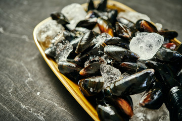 fresh delicious raw mussels served with ice on an old silver plate