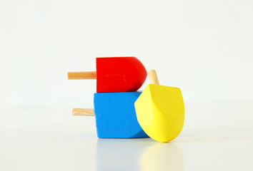 Image of jewish holiday Hanukkah with wooden dreidels colection (spinning top) over white background.
