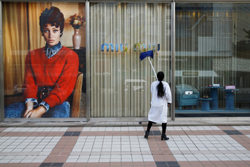 A woman cleans the shop window of a boutique of the Italian high fashion brand Miu Miu in Beijing