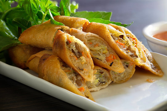 Fried Veg. spring rolls in white dish with vegetables on the dark wooden background