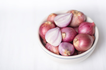 Red shallot in a bowl on white table, herb and spice, food ingredient