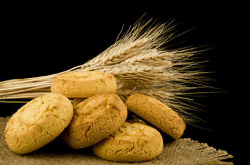 homemade cookies and spikelets of wheat isolated on black background close-up