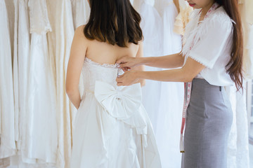 Asian bride trying on wedding dress,Woman designer fitting of dress making adjustment in fashion studio