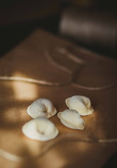 Ravioli or pelmeni on the craft paper and black background